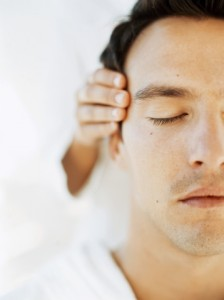 close-up of a young man getting a head massage from a massage therapist